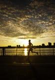 Mens die langs rivier bij zonsondergang loopt Stock Afbeeldingen