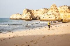 Mens die langs strand het Portugees lopen Stock Foto's