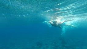 Mens die in langzame motie onder water zwemmen stock footage