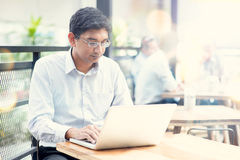 Mens die laptop computer met behulp van bij openluchtkoffie Stock Foto's