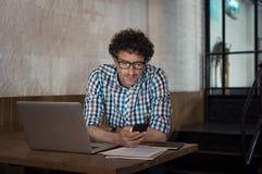Mens die laptop en smartphone gebruiken bij koffie stock foto's