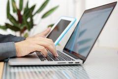 Mens die laptop en tabletpc tegelijkertijd met behulp van Stock Foto