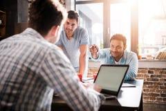 Mens die laptop met behulp van terwijl collega's die project, kleine commercieel vergaderingsconcept bespreken royalty-vrije stock foto