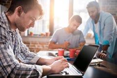 Mens die laptop met behulp van terwijl collega's die project, kleine commercieel vergaderingsconcept bespreken stock foto