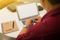 Mens die laptop op lijst met notaboek met behulp van stock afbeeldingen
