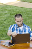 Mens die laptop in openlucht bekijken Stock Afbeelding