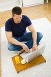 Mens die laptop thuis met behulp van Royalty-vrije Stock Fotografie