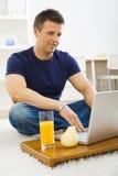 Mens die laptop thuis met behulp van stock foto