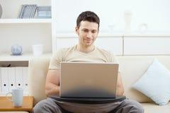 Mens die laptop thuis met behulp van Royalty-vrije Stock Afbeeldingen