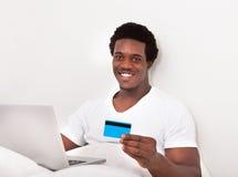 Mens die laptop voor online het winkelen met behulp van Royalty-vrije Stock Afbeelding