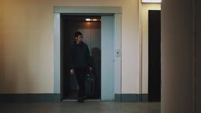 Mens die lift met koffer in de gang van het slaapzaalhuis opstappen stock videobeelden