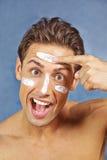 Mens die lotion toepassen op huid in gezicht stock foto