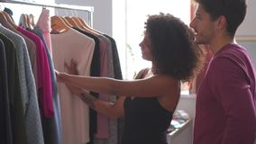 Mens die meisje helpen om kleding te selecteren stock videobeelden