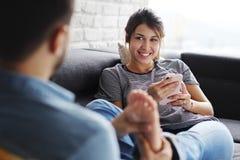 Mens die Meisjevoeten op Sofa At Home masseren Royalty-vrije Stock Foto's
