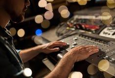 Mens die mengt console in de studio van de muziekopname gebruiken stock afbeelding