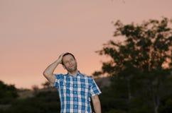 Mens die met één hand op zijn hoofd bij schemer denken Stock Fotografie
