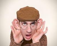 Mens die met afluisteraar luistert. Stock Afbeelding