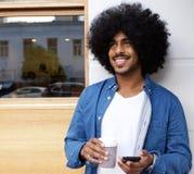 Mens die met afro zich buiten met de mobiele koffie van de telefoonadvertentie bevinden Royalty-vrije Stock Foto's