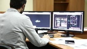 Mens die met baard blauwdrukken op computer maken stock footage