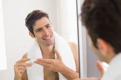 Mens die met bezinning vochtinbrengende crème op zijn gezicht zet Royalty-vrije Stock Fotografie