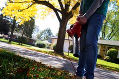 Mens die met bladventilator werken: de bladeren worden gewerveld op en neer op een zonnige dag Royalty-vrije Stock Afbeelding