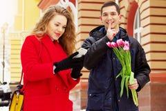 Mens die met bloemen een onverwachte verrassing voor zijn meisje voorbereiden Jong paar die samen door stadsstraten lopen royalty-vrije stock fotografie