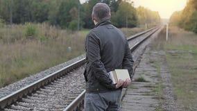 Mens die met boeken op trein dichtbij spoorweg wachten stock video