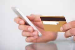 Mens die met creditcard en mobiele telefoon winkelt Stock Afbeelding