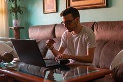 Mens die met creditcard op laptop thuis betalen stock foto's