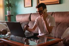 Mens die met creditcard op laptop thuis betalen stock fotografie