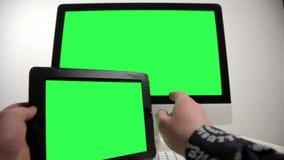 Mens die met de tablet en de computer werken stock videobeelden