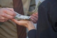 Mens die met dollars betaalt stock foto