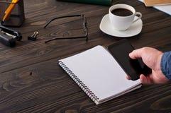 Mens die met een smartphone voor de bureau houten lijst werken Stock Afbeelding