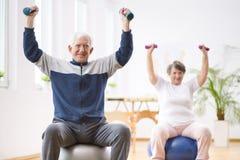 Mens die met gewichten in zijn pensioneringshuis uitoefenen royalty-vrije stock foto