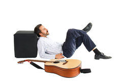 Mens die met gitaar vooraan ligt Stock Foto