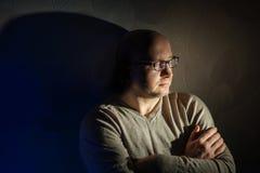 Mens die met glazen in de donkere ruimte zitten Stock Foto