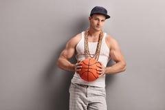 Mens die met gouden ketting een basketbal houden stock foto's