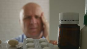 Mens die met Grote Hoofdpijn Pillen zoeken royalty-vrije stock fotografie