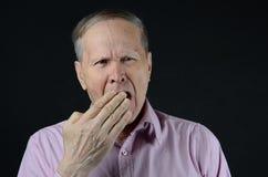 Mens die met hand geeuwen die zijn mond sluiten Stock Fotografie