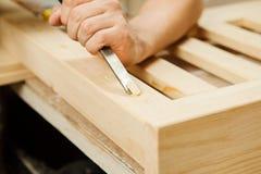 Mens die met het snijden van materiaal in de beitel van de workshopholding werken royalty-vrije stock foto