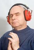Mens die met hoofdtelefoons aan muziek luistert Stock Afbeelding