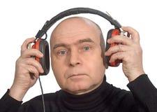 Mens die met hoofdtelefoons aan muziek luistert Stock Foto's