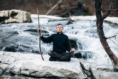 Mens die met klip op waterval zoals sensei mediteren Stock Foto's