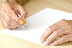 Mens die met kort potlood schrijft Stock Foto