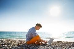 Mens die met laptop computer door de overzeese kust lopen Royalty-vrije Stock Foto's