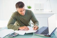 Mens die met laptop en het schrijven werken Stock Afbeeldingen