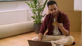 Mens die met laptop online bij nieuw huis winkelen stock video