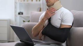Mens die met laptop in wapenslinger en cervicale kraag pijn in hals voelen, trauma stock footage