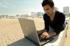 Mens die met laptop werkt Stock Foto