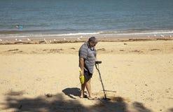 Mens die met metaaldetector zoeken op het strand met grote verwachtingen Stock Foto